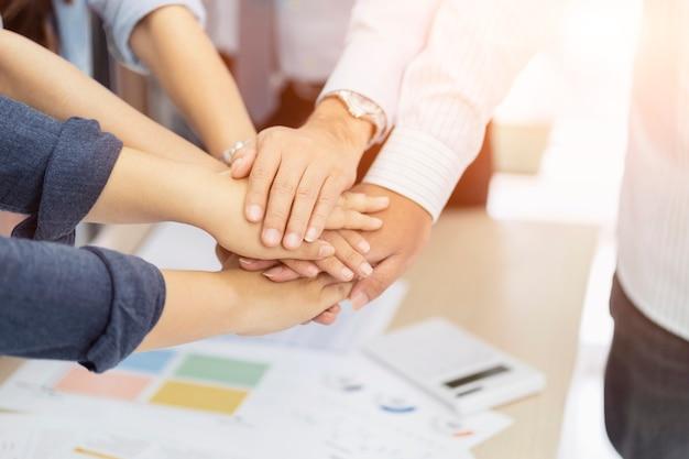 ビジネスチームワークが一緒に積み上げの密談で人々の手をグループ化します。