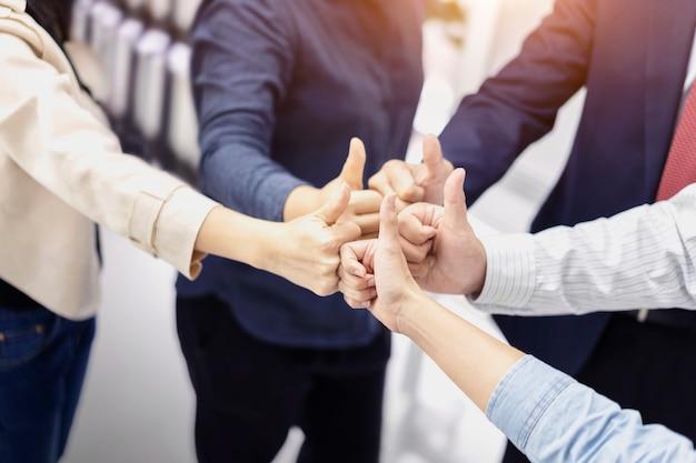 承認のジェスチャーを親指をあきらめてビジネス人々のグループ