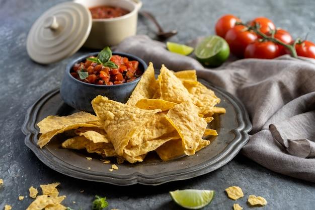 パーティー、メキシコ料理のナチョストルティーヤチップスとトマトのディップサルサのための軽食。