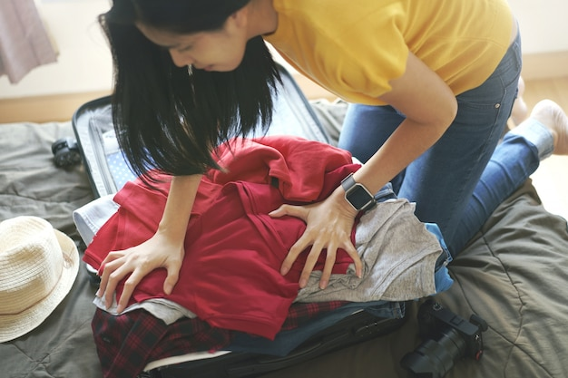女性はベッドの上のスーツケースバッグに服を詰め、新しい旅の準備をし、長い週末に旅行します。