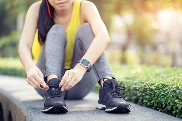 Обувь для бега - женщина завязывает шнурки, спортивный фитнес бегун готовится к пробежке в саду.