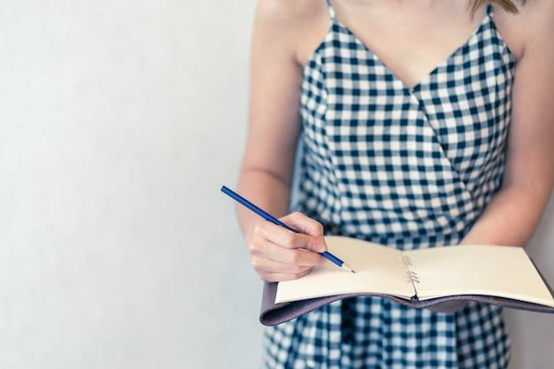 アジアの女性のノートブック日記の概念と作業計画の概念を書く