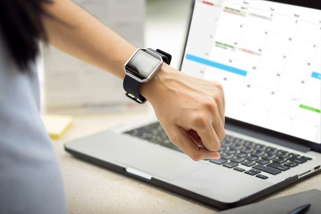 腕時計のスマートな腕時計を持つ女性の手。