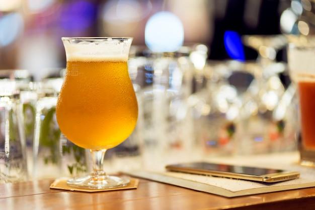 夜のクラブでバーカウンターでスマートフォンと軽いビールのグラス。