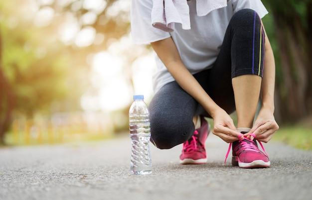 Обувь для бега - женщина завязывает шнурки. женский спортивный фитнес бегун готовится для пробежки в саду.