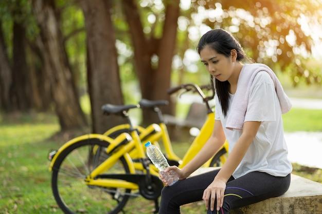 若い女性は、健康的な概念の庭で運動を終えたときに休んで、トレーニングと水のボトルを保持しようとしました。