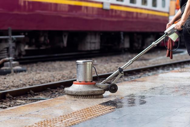 床を掃除して磨くためにスクラバーマシンを使用する労働者。鉄道駅の清掃メンテナンス列車。