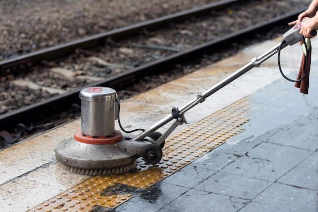 Работник использует скруббер для очистки и полировки пола. уборка технического обслуживания поезда на железнодорожной станции.