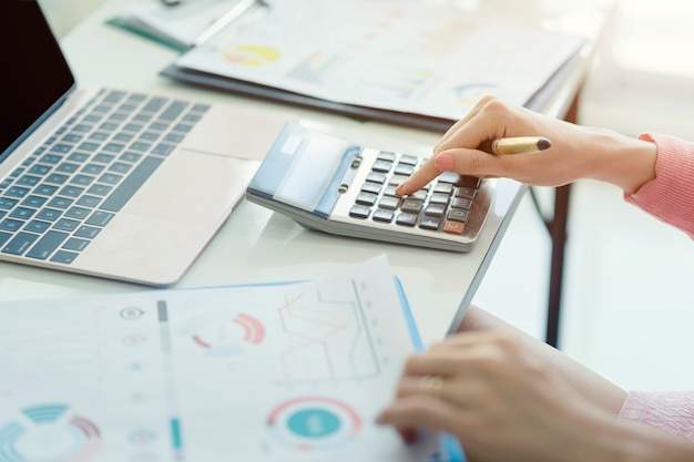 グラフとドキュメント財務データレポートを使用したビジネス分析でアカウントに取り組んでいる女性会計士