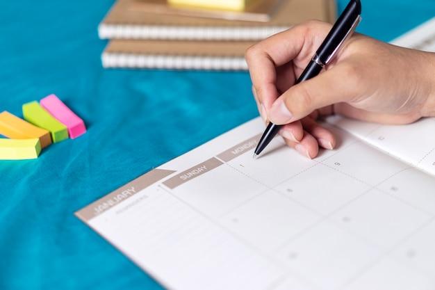 Повестка дня и график планирования женщина, используя календарь событий
