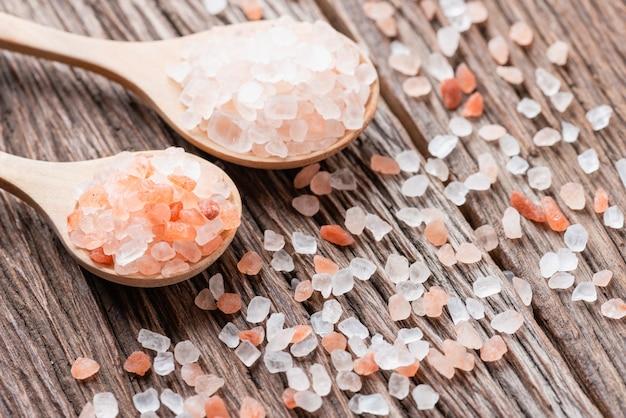木のスプーンに白い塩とヒマラヤピンクの塩の結晶