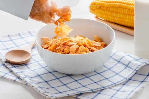 シリアルコーンフレークをボウルに注ぐ、健康的な朝食、毎日の食事。