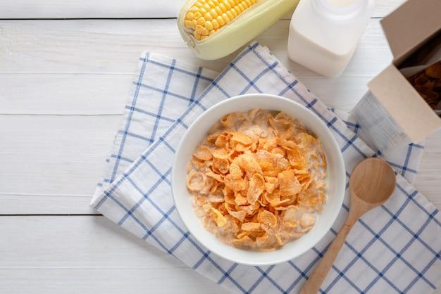 ボウルに牛乳とシリアルのコーンフレークボックス、エネルギーの健康、朝食の毎日の食事とコーンフレーク。コピースペースのトップビュー。