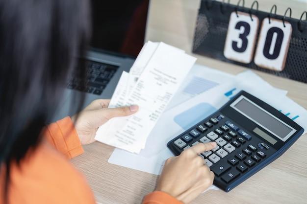 Женщина нажимает калькулятор и рассчитать стоимость счета для решения финансов и доходов.