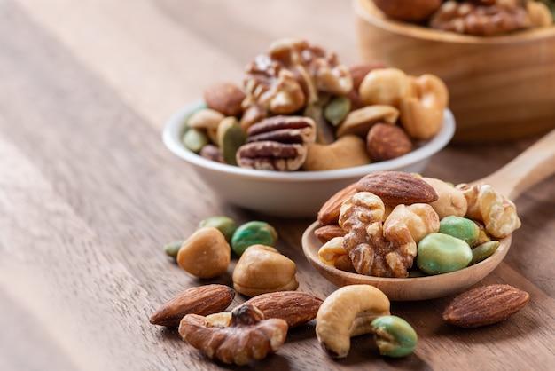 木のスプーン、各種のナッツのナットミックス、コピースペース。