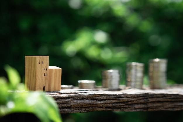 木の家モデルとコインマネーの木のテーブルにぼかし緑の葉自然のバックグラウンド