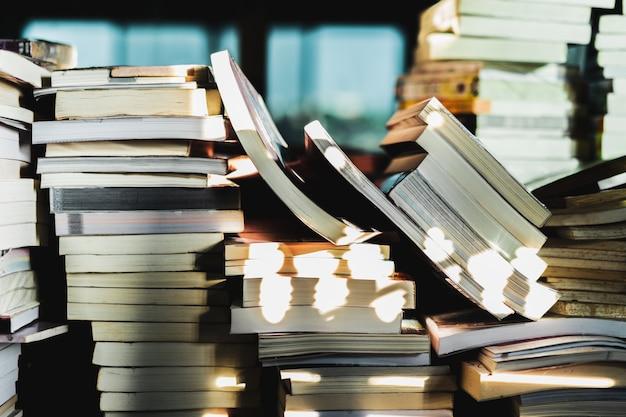 木製のテーブル、学習および教育の概念に関する古書のスタック。