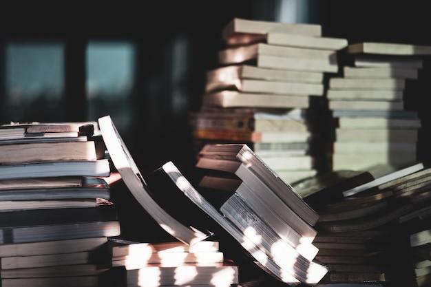 木製のテーブル、学習および教育の概念に関する古書のスタック。セレクティブフォーカス