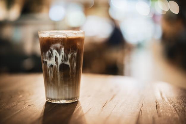 ビンテージスタイルのコンセプトを持つ木製の背景にアイスコーヒー。