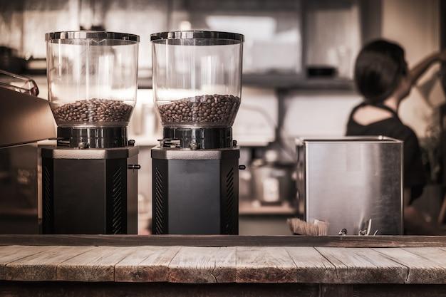 コーヒーショップのコーヒーマシンでコーヒー豆の前に木製のテーブル