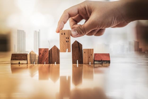 Рука выбирая мини модель деревянного дома от модели на деревянный стол