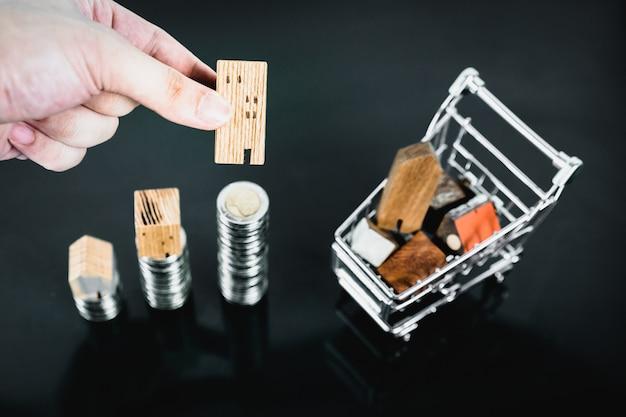 Рука, выбирая мини деревянный дом из ряда монет деньги с тележкой на темном столе