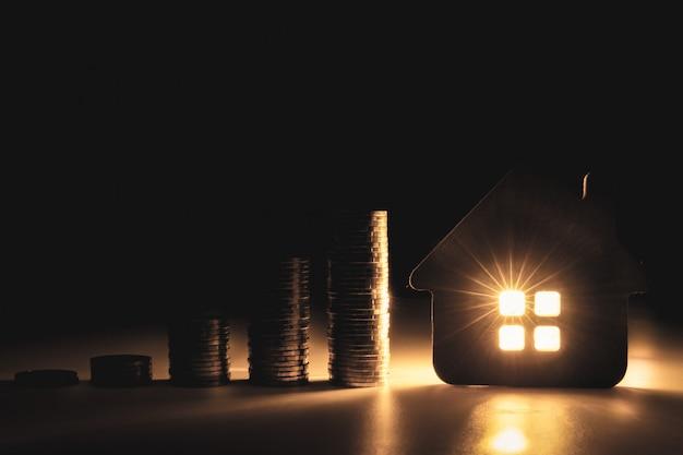 Модель дома и ряд монетных денег на белом столе