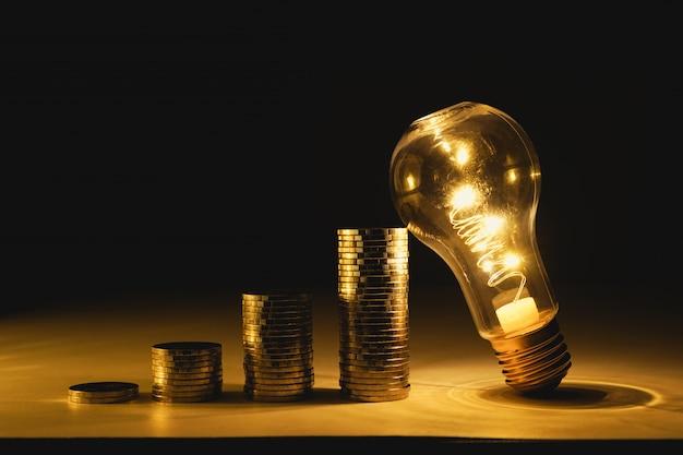 お金の会計を節約するためのコインのヒープ階段の電球。