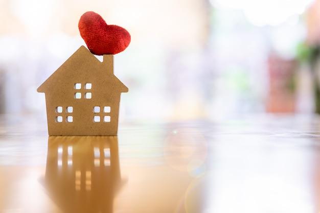 Модель дома и сердца на деревянном столе, символ для строительства