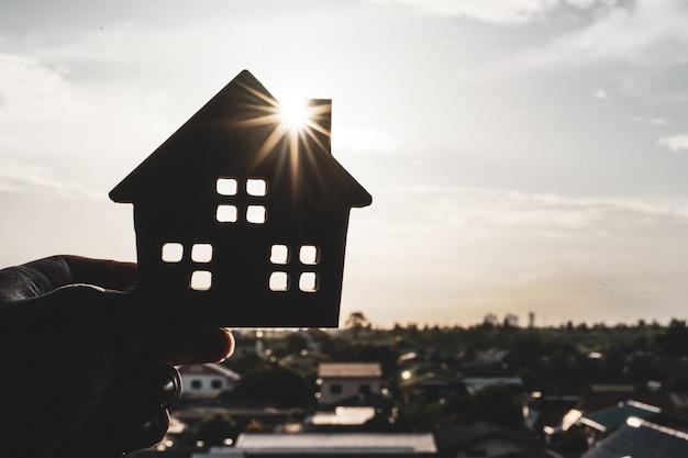 住宅保険ブローカーの代理人の手またはセールスマンの人の家モデル