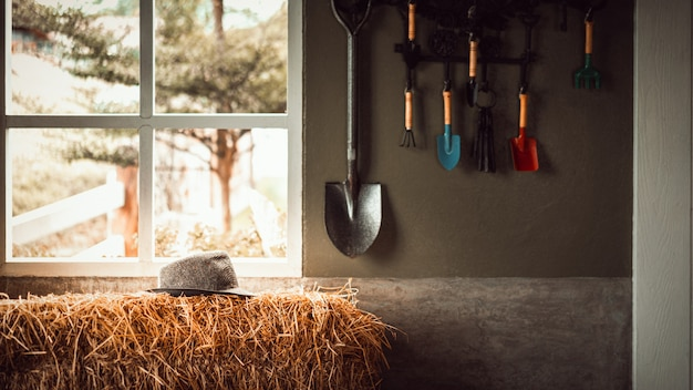 小屋の壁に掛かっているガーデンツールとわらのスタックに麦わら帽子