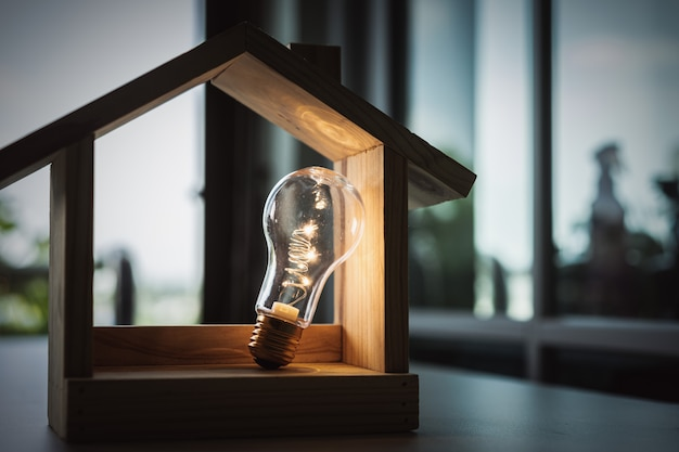 テーブルの上の木の家、建設のためのシンボルと電球