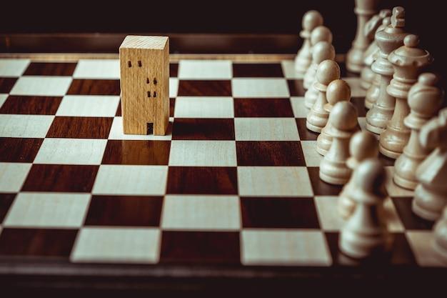 チェスゲームで建物と家のモデルにチェスを移動するビジネスマンの手