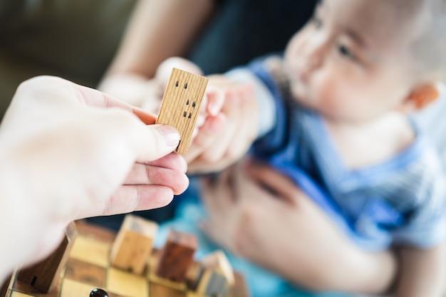 赤ちゃんの手は母親の手で家のモデルを保持しています。