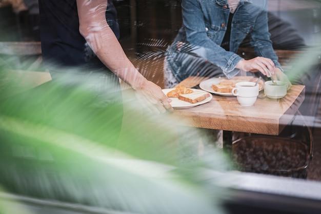 朝食、コーヒー、バターとジャム付きトーストを食べる女性