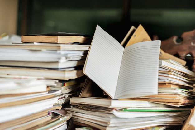 木製のテーブル上の古い本のスタックとメモ帳