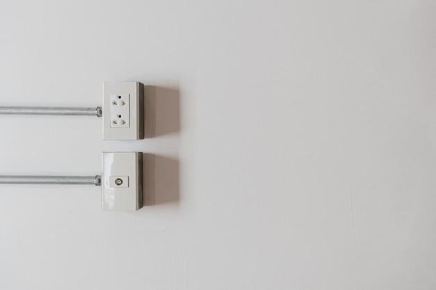 白い壁に差し込まれている電源コードケーブル用の壁コンセント
