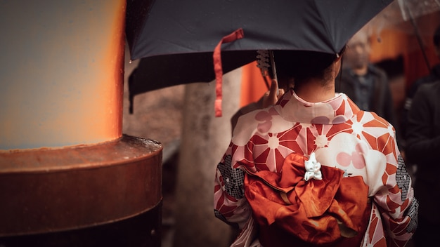 Женщина в красном кимоно и зонтик в саду парка киото, япония