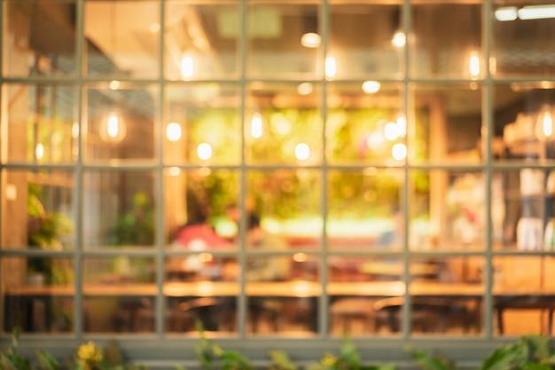 夜のライトゴールドとカフェ(レストラン)のぼやけ。現代のライフスタイルの背景。