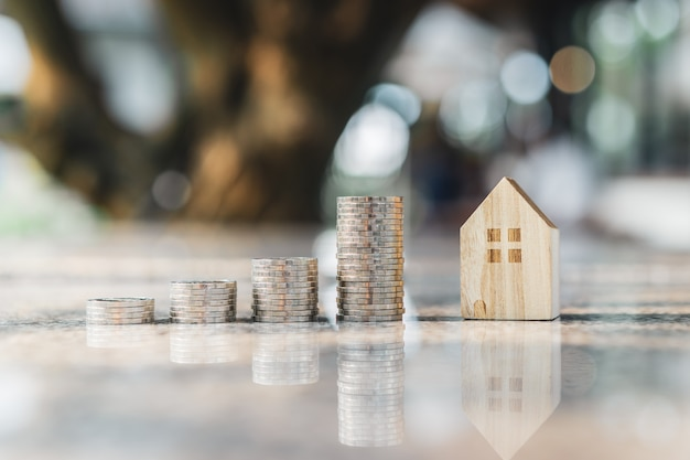 Модель деревянного дома и ряд монетных денег на белом фоне,