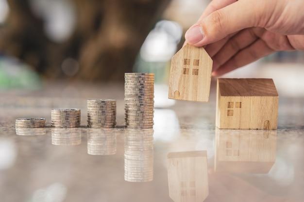 Рука, выбирая мини модель деревянного дома из модели и ряд монетных денег на деревянный стол