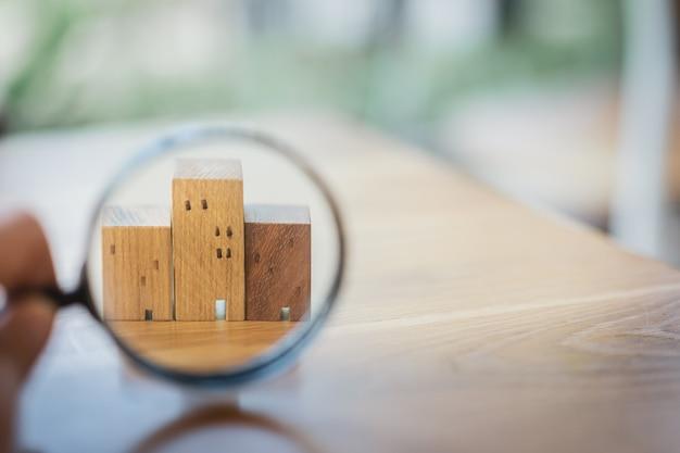 Рука держит увеличительное стекло и смотрит на модель дома