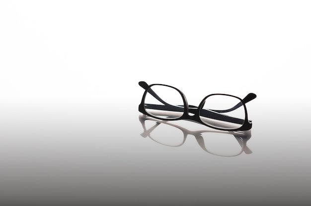 Очки в черной оправе на зеркальном фоне