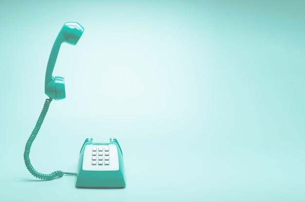 ティールグリーンの背景にレトロなグリーン電話