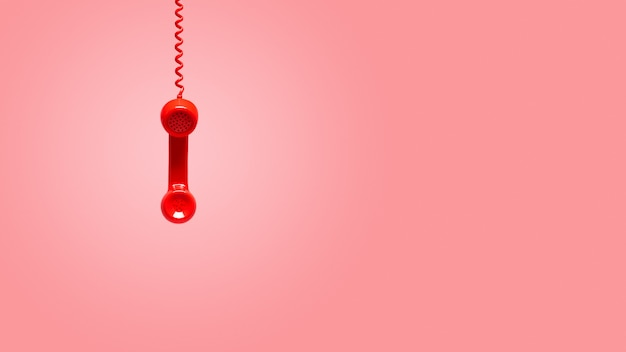 ピンクの背景に掛かっている赤い古い受話器