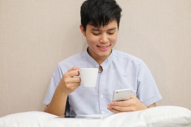 Закрыть молодой азиатский человек, играть в смартфон и проведение чашку чая на кровати перед сном