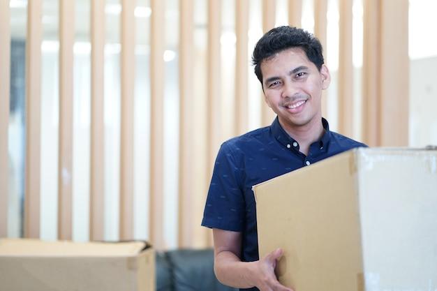 クローズアップ古い手から新しい家または住居への移動のための大きい箱を運ぶ人の手