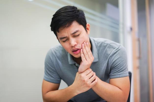歯痛、歯科のコンセプトから痛みを感じるアジア人男性を閉じます