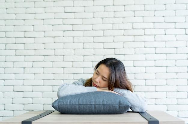 リビングルームで枕で眠っている若い女性を閉じます