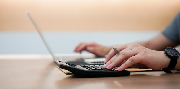 Рука работника бухгалтера человек нажимает на калькулятор и набирает клавиатуру на ноутбуке